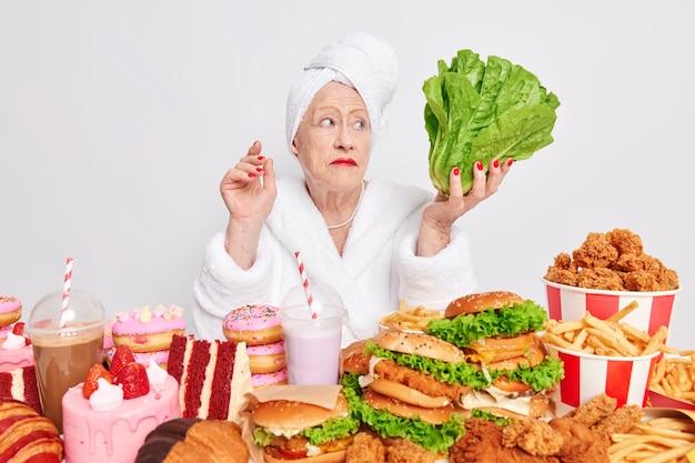 Poważna stara kobieta z pomarszczoną skórą, czerwony manicure trzyma się diety, uważnie przygląda się zielonym warzywom