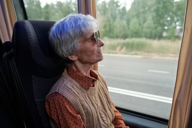 Poważna starsza kaukaska kobieta w okularach przeciwsłonecznych patrząca przez okno podczas jazdy autobusem