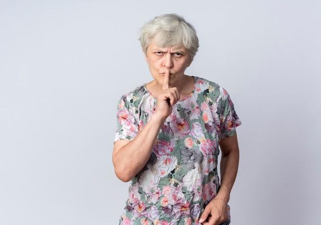 Poważna starsza kobieta kładzie palec na ustach, gestykulując cicho cichy znak na białym tle na białej ścianie