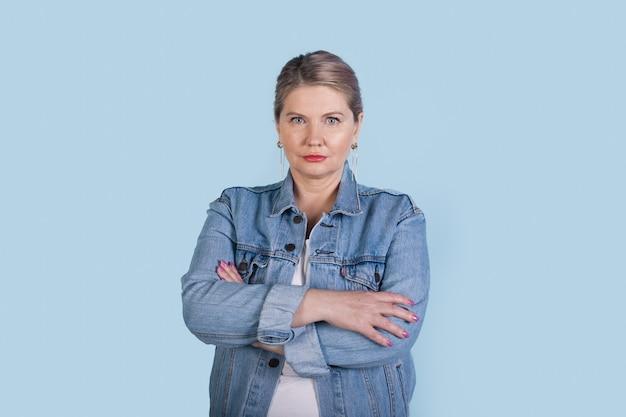 Poważna starsza kobieta o blond włosach, ubrana w dżinsowy płaszcz z skrzyżowanymi rękami na niebieskiej ścianie studia