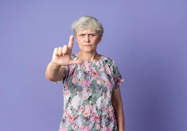 Poważna starsza kobieta wskazuje na białym tle na fioletowej ścianie