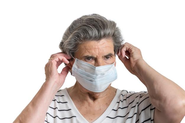 Poważna starsza pani chroniąca maską medyczną