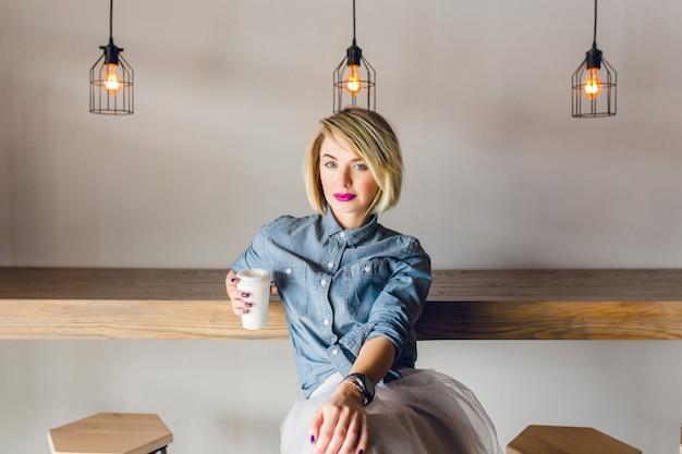 Poważna stylowa dziewczyna o blond włosach i różowych ustach siedzi w kawiarni z drewnianymi krzesłami i stołem. trzyma filiżankę kawy