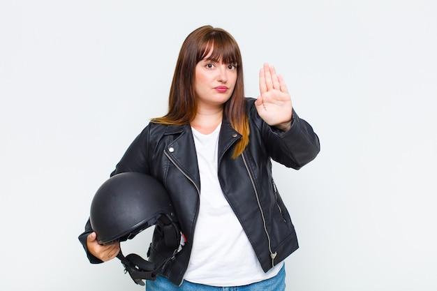 Poważna, surowa, niezadowolona i wściekła kobieta dużych rozmiarów pokazuje otwartą dłoń wykonującą gest stop