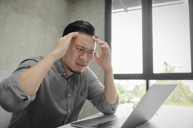 Poważna twarz mężczyzna pracuje na laptopie samotnie w pokoju.