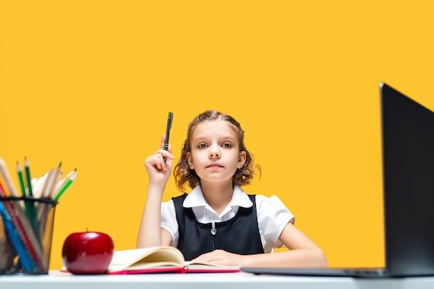 Poważna uczennica podnosząca rękę z długopisem siedzącym przy biurku z edukacją na odległość na laptopie