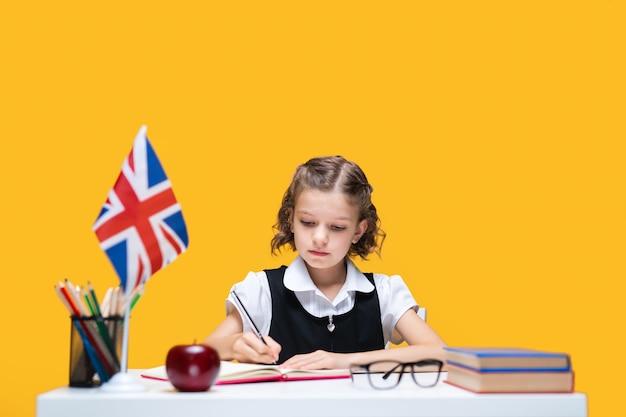 Poważna uczennica w masce odrabiająca pracę domową w zeszycie ucząca się angielskiego nauczania na odległość