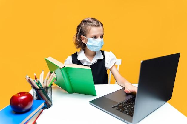 Poważna uczennica w masce odrabiająca pracę domową z książką i laptopem na odległość