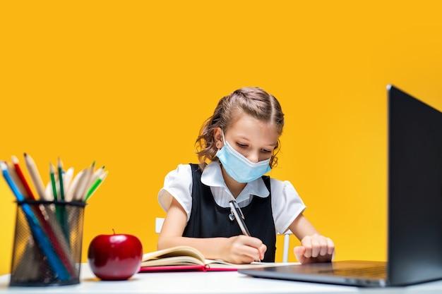 Poważna uczennica w masce odrabiająca pracę domową z pisaniem na laptopie w notebooku kształcenie na odległość
