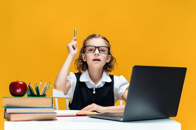 Poważna uczennica w okularach podnosząca pióro do góry siedząca przy biurku z edukacją na odległość na laptopie