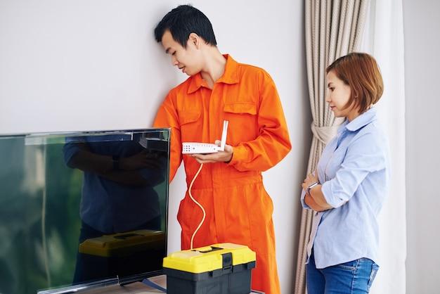 Poważna wietnamska gospodyni domowa patrzy na majsterkowicza z ruterem wi-fi za telewizorem