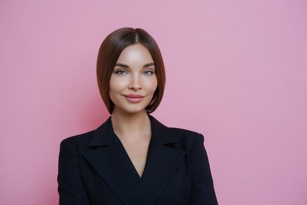 Poważna zadowolona brunetka europejska w czarnych ubraniach jest pewna siebie i zadowolona