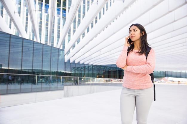 Poważna zadumana studencka dziewczyna opowiada na telefonie z satchel