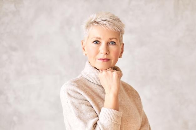 Poważna zamyślona kobieta w średnim wieku ubrana w ciepły sweter i patrzące perłowe kolczyki