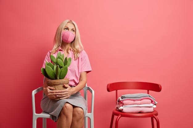 Poważna zamyślona kobieta w średnim wieku, ubrana w ochronną maskę na twarz, myśli o bezpieczeństwie podczas pandemii trzyma doniczkowego kaktusa, samotnie siedzi na krześle, zostaje w domu w okresie kwarantanny. covid 19 dystans społeczny
