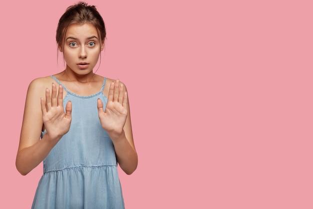 Poważna zdziwiona dziewczyna bez gestu wyciąga dłonie, zaprzecza randce z nieznajomym, robi znak stopu, ma zmartwioną minę