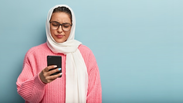 Poważna zdziwiona kobieta o specyficznym wyglądzie, jest bardzo religijna, nosi biały szal, spogląda z zakłopotaniem na smartfona, czyta dziwną wiadomość, odizolowana na niebieskiej ścianie, pusta przestrzeń
