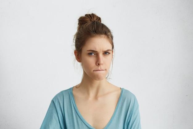 Poważna, zła kobieta marszcząca brwi, zaciskająca usta razem ze złością, próbująca panować nad sobą, a jej emocje nie okazują rozdrażnienia i złości.