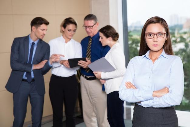 Poważne businesswoman stojących z przodu działalności zespołu