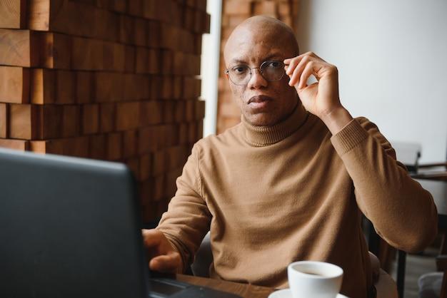 Poważne czarne męskie okulary studenckie robienia notatek siedząc przy stole z laptopem i pracy nad projektem w przytulnej kawiarni.