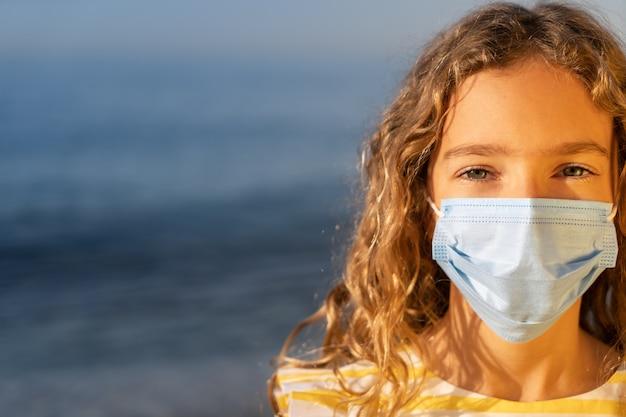 Poważne dziecko noszenie maski medycznej na zewnątrz na tle błękitnego nieba
