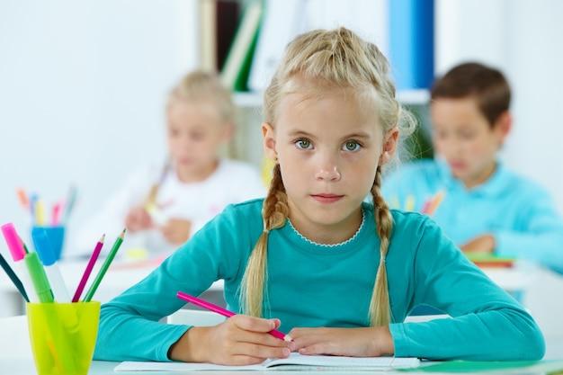 Poważne dziewczynka gospodarstwa różowy ołówek