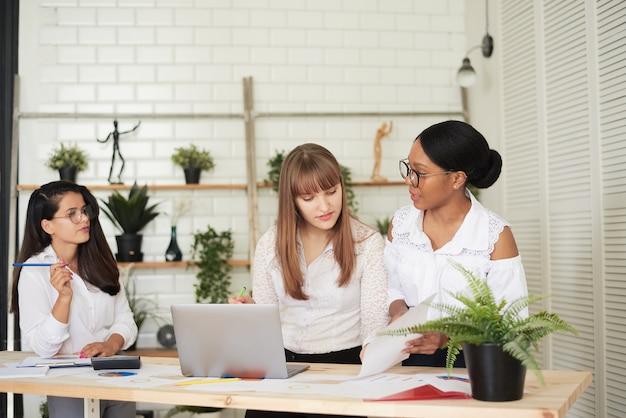 Poważne kobiece wielorasowe zespoły rozwiązujące wspólnie problemy, różnorodni skoncentrowani afrykańscy, azjatyccy i kaukascy koledzy omawiają burzę mózgów nad projektem, pracę na laptopie, kreatywną pracę zespołową w biurze.