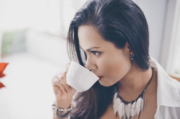 Poważne kobieta picia z kubka kawy