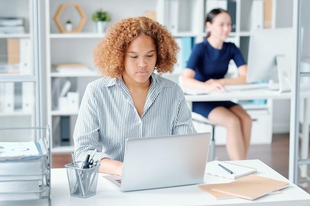 Poważne kręcone młoda bizneswoman siedzi przy biurku przed laptopem