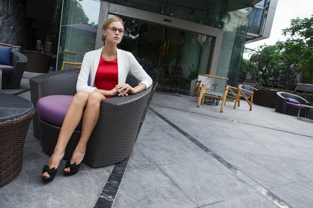 Poważne młoda kobieta siedzi na zewnątrz kawiarni