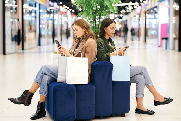 Poważne młode kobiety siedzące na pufach w holu centrum handlowego i korzystające ze smartfonów w poszukiwaniu specjalnych ofert zakupów