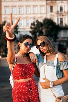 Poważne młode kobiety w letnim stroju i okularach przeciwsłonecznych spędzające razem miło czas