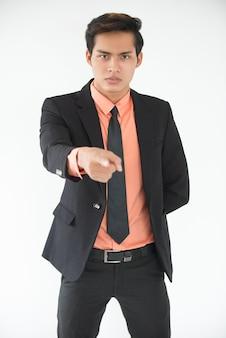Poważne młody biznesmen, wskazując na aparat