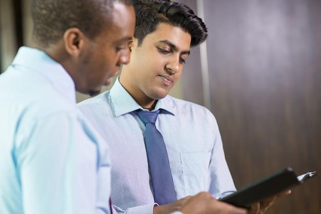 Poważne młodzi adwokaci czytający szczegóły sprawy