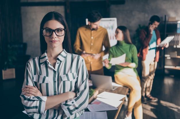Poważne pewnie kobieta stojąca z rękami skrzyżowanymi na sobie okulary w pasiastej koszuli na tle jej współpracowników omawiających strategię uruchamiania