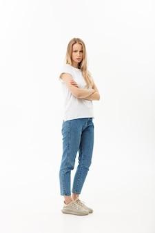 Poważne pewnie młoda kobieta z długimi blond włosami ubrana w casual stojący patrząc w kamerę, całe ciało na białym.