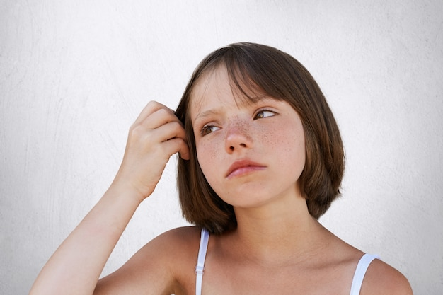 Poważne piegowate dziecko, trzymające rękę na włosach, o zamyślonym wyrazie twarzy, odwracające wzrok. piękna dziewczyna pozuje przeciw biel ścianie. piękno, dzieciństwo, koncepcja wyrazu twarzy