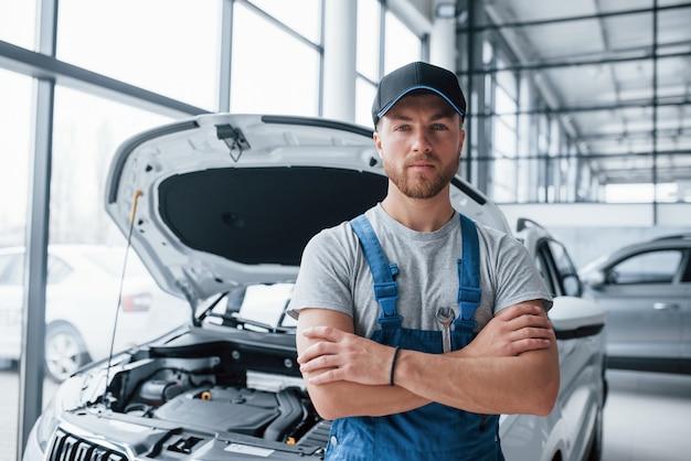 Poważne spojrzenie. pracownik w niebieskim mundurze stoi w salonie samochodowym