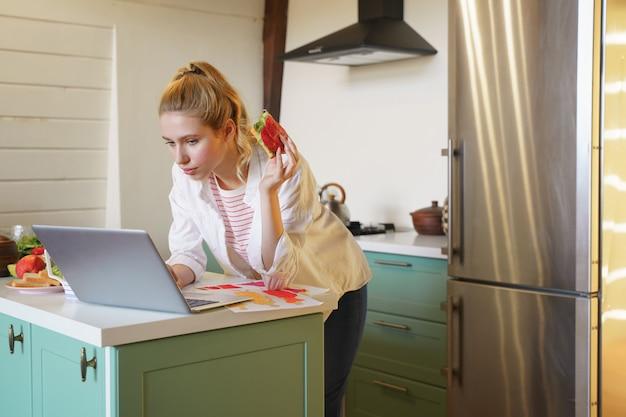 Poważne zadanie. urocza blondynka trzymająca kanapkę w dłoni, patrząc na komputer