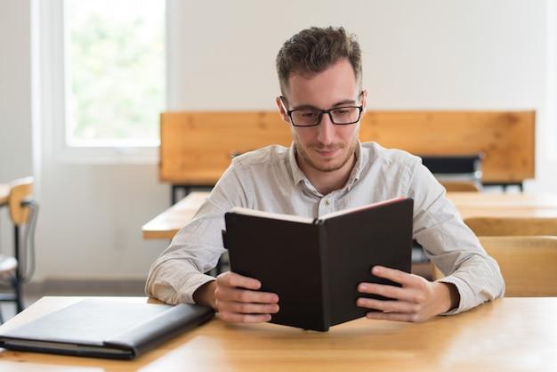 Poważnego męskiego ucznia czytelniczy podręcznik przy biurkiem w sala lekcyjnej