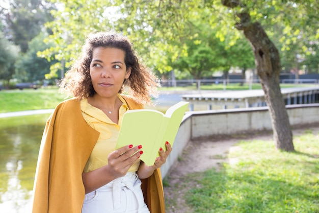 Poważnej młodej kobiety czytelnicza książka w miasto parku