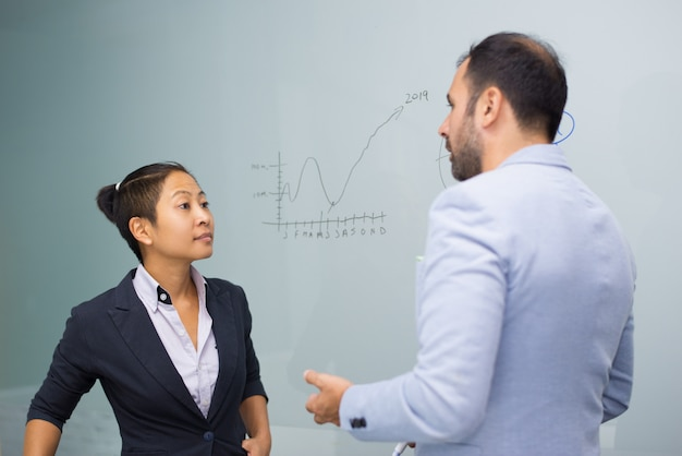Poważni biznesowi koledzy stoi przy deską i opowiadać