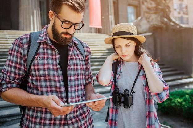 Poważni i skoncentrowani turyści stoją na schodach. trzyma tablet w ręce. oboje na to patrzą. młoda kobieta trzymać koronki z lornetki. podróżujący są bardzo troskliwi.