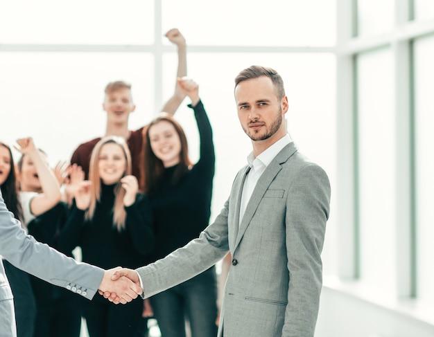 Poważni młodzi mężczyźni ściskający ręce koncepcja współpracy