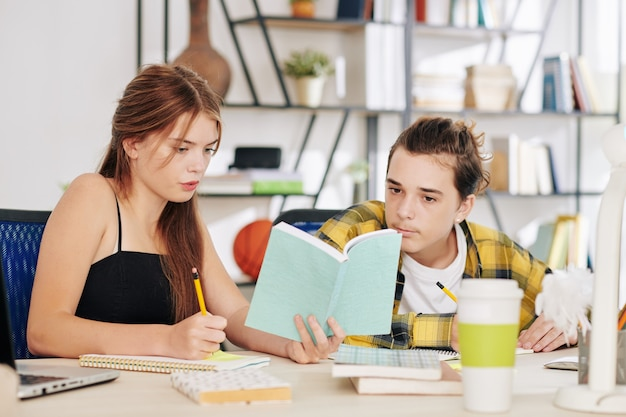 Poważni nastoletni uczniowie czytający książki i piszący wypracowania na lekcjach języka angielskiego