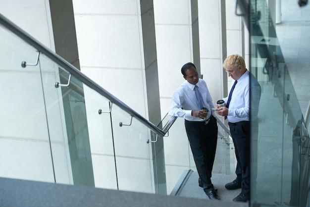 Poważni przedsiębiorcy stojący na schodach pijący kawę