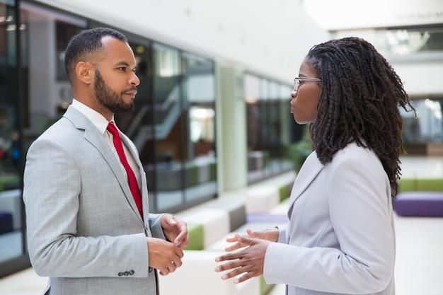 Poważni różnorodni partnerzy biznesowi spotykają się w hali biurowej