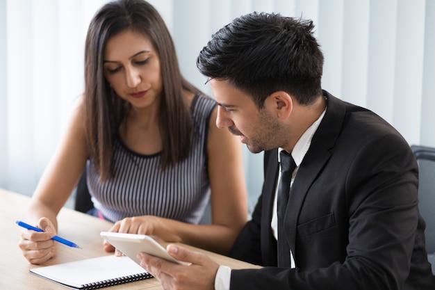 Poważni ruchliwie młodzi biznesowi koledzy dyskutuje agendę