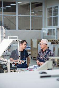 Poważni starsi i młodzi współpracownicy stoją przy prasie drukarskiej i omawiają dopasowanie kolorów do druku