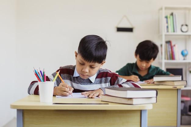 Poważni studenci z azji uczący się w klasie podczas lekcji